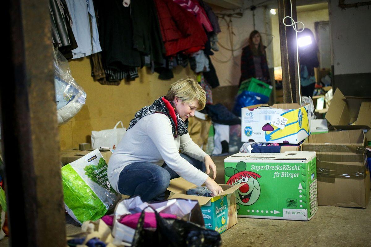Fabienne Matagne beim Aussortieren von Kleidern.