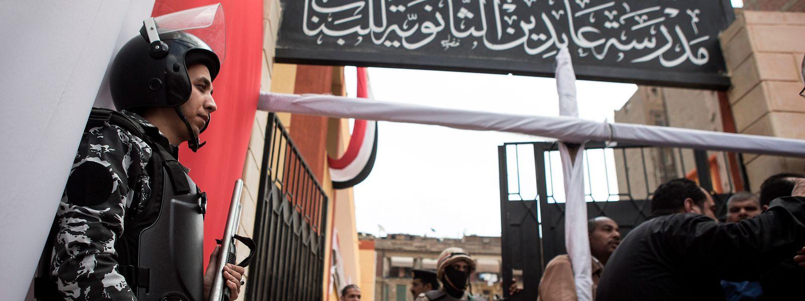 In Kairo gehen Menschen für ein Referendum über neue Machtbefugnisse für Ägyptens Präsidenten Al-Sisi zur Wahl. Vor den Wahllokalen stehen Polizisten.