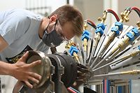 A mechanic adjusts a nozzle in a heat flux test stand at Rocket Factory Augsburg in Augsburg, southern Germany on June 16, 2021. - Rocket Factory Augsburg is developing a low cost space rocket designed to transport micro sattelites to their desitanted orbits. Car-manufacturing powerhouse Germany could soon be set for take-off in the space sector as it looks to ride a boom in mini-launchers for small satellites and compete with major US firms such as SpaceX. (Photo by LENNART PREISS / AFP) / TO GO WITH AFP STORY by Jean-Philippe LACOUR
