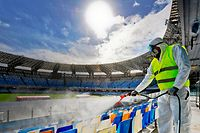 Picture taken on March 4, 2020 shows cleaners wearing a protective suit, as they sanitise the seats of the San Paolo stadium in Naples. - Italy ordered on March 4 that all major sporting events be held behind closed doors until April 3 as the country grapples with the deadly coronavirus outbreak. The government decision was announced moments after health officials said the death toll from COVID-19 had jumped to 107 and the number of cases had passed 3,000. (Photo by CIRO FUSCO / ANSA / AFP) / - Italy OUT