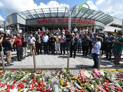 TOPSHOT - People pray on July 24, 2016 at a memorial of candles and flowers in front of the Olympia Einkaufszentrum shopping centre in Munich, southern Germany, where an 18-year-old German-Iranian student run amok. Europe reacted in shock to the third attack on the continent in just over a week, after David Ali Sonboly went on a shooting spree at a shopping centre on July 22, 2016 in what appears to have been a premeditated attack, before turning the gun on himself. / AFP PHOTO / Christof Stache