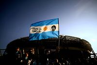 """A man waves the flag of Argentina with a photo of late Argentinian football legend Diego Maradona, on November 26, 2020 outside the San Paolo stadium in Naples as he and others come to mourn the death of Maradona. - Maradona, widely remembered for his """"Hand of God"""" goal against England in the 1986 World Cup quarter-finals, died on November 25, 2020 of a heart attack at his home near Buenos Aires in Argentina, while recovering from surgery to remove a blood clot on his brain. (Photo by Filippo MONTEFORTE / AFP)"""