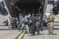 """In this handout image courtesy of the US Marine Corps, Families begin to board a US Air Force Boeing C-17 Globemaster III during an evacuation at Hamid Karzai International Airport, Kabul, Afghanistan, August 23, 2021. (Photo by Samuel RUIZ / US MARINE CORPS / AFP) / RESTRICTED TO EDITORIAL USE - MANDATORY CREDIT """"AFP PHOTO / SAMUEL RUIZ / US MARINE CORPS """" - NO MARKETING - NO ADVERTISING CAMPAIGNS - DISTRIBUTED AS A SERVICE TO CLIENTS"""