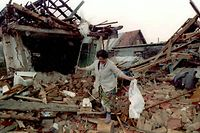 ARCHIV - 09.04.1995, Bosnien-Herzegowina, Sarajevo: Die bosnische Muslima Ziba Suba sucht in den Trümmern ihres bei einem serbischen Angriff zerstörten Wohnhauses nach den letzten Habseligkeiten. Der Bosnienkrieg (1992-1995) ist der blutigste der Konflikte nach dem Zerfall des Vielvölkerstaates Jugoslawien in den 1990er Jahren. Die Zahl der Todesopfer wird mit 100 000 beziffert, Hunderttausende wurden verletzt. Fast jeder zweite der 4,3 Millionen Einwohner - 1,8 Millionen - verlor seine Heimat. (zu dpa «Bosniens unfertiger Frieden - Das Abkommen von Dayton wird 25») Foto: Anja Niedringhaus/epa/dpa +++ dpa-Bildfunk +++