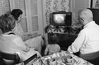(FILES) In this file photo taken on July 21, 1969, a family in Paris watches as US astronaut Neil Armstrong commander of Apollo 11, sets his foot on the moon July 20, 1969 in Paris. (Photo by STR / AFP)