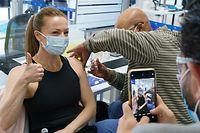 26.04.2021, Kanada, Montreal: Ein Mitarbeiter filmt die Impfung einer Kollegin in einer COVID-19-Impfklinik am CAE-Hauptsitz. Im Montrealer Hauptquartier des Flugsimulationstechnologie-Herstellers begann ein Programm der Provinz zur Durchführung von Impfungen in großen Unternehmen. Foto: Paul Chiasson/The Canadian Press via ZUMA/dpa +++ dpa-Bildfunk +++