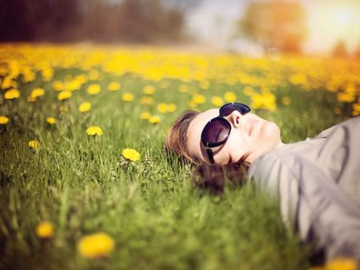 Little girl lying down in a field filled with white dandelions, with eyes closed and a happy smile.