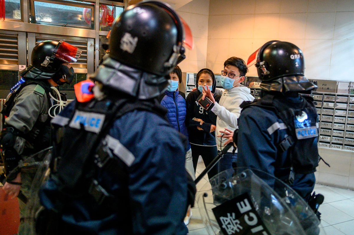 TOPSHOT - People argue with riot police inside the lobby of a residential building as residents protest against plans for an empty local housing estate to become a temporary quarantine camp for patients and frontline medical staff of a SARS-like virus outbreak which began in the Chinese city of Wuhan, in the Fanling district in Hong Kong on January 26, 2020. - Protesters threw petrol bombs on January 26 night at an empty public housing complex in Hong Kong that had been earmarked to become a temporary quarantine zone as the city battles the outbreak of a SARS-like virus. (Photo by Philip FONG / AFP)