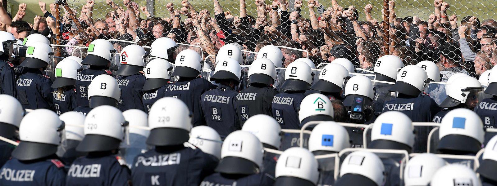 Polizisten bei der Grenzschutzübung. Als Flüchtlinge (hinterm Zaun) posieren Polizeischüler.