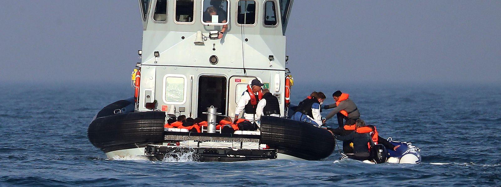 Britische Grenzschutzbeamte helfen einer Gruppe mutmaßlicher Migranten an Bord der HMC Hunter.