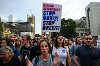 Anti-Brexit demonstrators hold placards as they take part in a protest march from Britain's Houses of Parliament to Downing Street in London on August 28, 2019. - British Prime Minister Boris Johnson announced Wednesday that the suspension of parliament would be extended until October 14 -- just two weeks before the UK is set to leave the EU -- enraging anti-Brexit MPs. MPs will return to London later than in recent years, giving pro-EU lawmakers less time than expected to thwart Johnson's Brexit plans before Britain is due to leave the European Union on October 31. (Photo by DANIEL SORABJI / AFP)