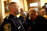 TOPSHOT - Protestors try to enter the Michigan House of Representative chamber and are being kept out by the Michigan State Police after the American Patriot Rally organized by Michigan United for Liberty protest for the reopening of businesses on the steps of the Michigan State Capitol in Lansing, Michigan on April 30, 2020. - The group is upset with Michigan Gov. Gretchen Whitmer's mandatory closure to curtail Covid-19. (Photo by JEFF KOWALSKY / AFP)