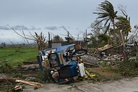 TOPSHOT - An overturned tricycle is seen next to a destroyed house after Super Typhoon Mangkhut hit the town of Alcala, Cagayan province on September 15, 2018. - Super Typhoon Mangkhut smashed through the Philippines on September 15, as the biggest storm to hit the region this year claimed the lives of its first victims and forced tens of thousands of people from their homes. (Photo by TED ALJIBE / AFP)