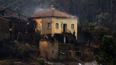 A man stands in the stairway of a house with smoke billowing from the roof in an area devastated by a wildfire in Canical, near Alvares, on May 18, 2017. A wildfire in central Portugal killed at least 57 people and injured 59 others, most of them burning to death in their cars, the government said on June 18, 2017. Several hundred firefighters and 160 vehicles were dispatched late on June 17 to tackle the blaze, which broke out in the afternoon in the municipality of Pedrogao Grande before spreading fast across several fronts.    / AFP PHOTO / MIGUEL RIOPA