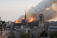TOPSHOT - Smoke billows as flames burn through the roof of the Notre-Dame de Paris Cathedral on April 15, 2019, in the French capital Paris. - A huge fire swept through the roof of the famed Notre-Dame Cathedral in central Paris on April 15, 2019, sending flames and huge clouds of grey smoke billowing into the sky. The flames and smoke plumed from the spire and roof of the gothic cathedral, visited by millions of people a year. A spokesman for the cathedral told AFP that the wooden structure supporting the roof was being gutted by the blaze. (Photo by Fabien Barrau / AFP)