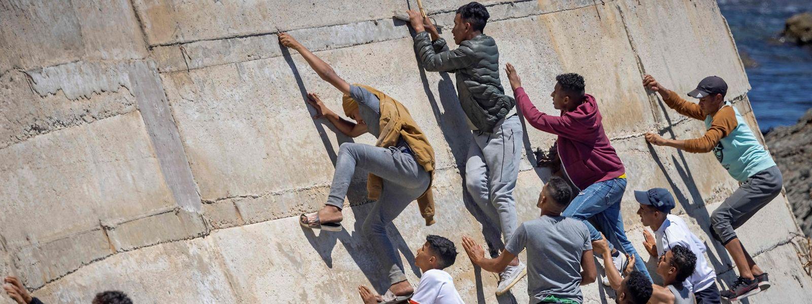 Migranten klettern eine Wand im marokkanischen Fnideq hoch, um anschließend zur spanischen Enklave Ceuta zu gelangen.