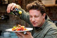 """ARCHIV - 06.12.2017, Hamburg: Der britische Starkoch Jamie Oliver kocht in der One Kitchen Kochschule. Die Restaurantkette von Jamie Oliver, Jamie's Italian, hat in Großbritannien Insolvenz angemeldet. (zu dpa """"Restaurantkette von Starkoch Jamie Oliver ist insolvent"""") Foto: Axel Heimken/dpa +++ dpa-Bildfunk +++"""