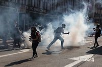 Protesters react after police fired tear gas to disperse them in the Sai Wan Ho district in Hong Kong on November 11, 2019. - A police officer shot a masked protester in an incident shown live on Facebook and a man was set on fire on November 11 during one of the most violent days of clashes in Hong Kong since pro-democracy unrest erupted more than five months ago. (Photo by DALE DE LA REY / AFP)