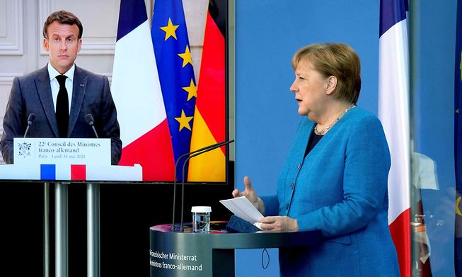 French President Emmanuel Macron is seen on a video screen during a joint press conference with German Chancellor Angela Merkel as part of a virtual Plenary Session of the Franco-German Council of Ministers in Berlin, on May 31, 2021.