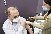 A medical worker holds a syringe to give a jab with the AstraZeneca vaccine against the Covid-19 coronavirus to a patient, at a vaccination centre in Vantaa, Finland on March 11, 2021. - Around 540 000 people have received at least one vaccination dose against the Covid-19 coronavirus in Finland. (Photo by Markku Ulander / Lehtikuva / AFP) / Finland OUT