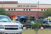 """Emergency crews gather in the parking lot of Santa Fe High School where at least eight students were killed on May 18, 2018 in Santa Fe, Texas.  At least eight people were killed when a student opened fire at his Texas high school on May 18, 2018, as President Donald Trump expressed """"heartbreak"""" over the latest deadly school shooting in the United States. The shooting took place as classes were beginning for the day at Santa Fe High School in the city of the same name, located about 30 miles (50 kilometers) southeast of Houston.""""There are multiple fatalities,"""" Harris County Sheriff Ed Gonzalez told reporters. """"There could be anywhere between eight to 10, the majority being students.""""      / AFP PHOTO / Daniel KRAMER"""