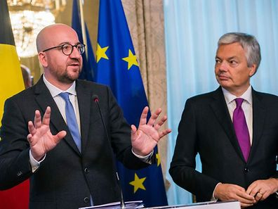 Belgium's Prime Minister Charles Michel (L), flanked by Belgium's Foreign Minister Didier Reynders (R), gestures as he speaks during a press conference following an emergency meeting of all Belgium federal entities on the EU-Canada Comprehensive Economic and Trade Agreement (CETA) in Brussels on October 24, 2016. The small Belgian region refused on October 24 to bow to growing pressure to back the key trade deal with Canada, heightening tensions within Belgium and Europe as well as with historic allies in North America. Riding a rising wave of Western populist distrust of international trade deals, French-speaking Wallonia's parliament stuck to its refusal to heed a late Monday EU deadline to support the pact. / AFP PHOTO / BELGA / LAURIE DIEFFEMBACQ / Belgium OUT