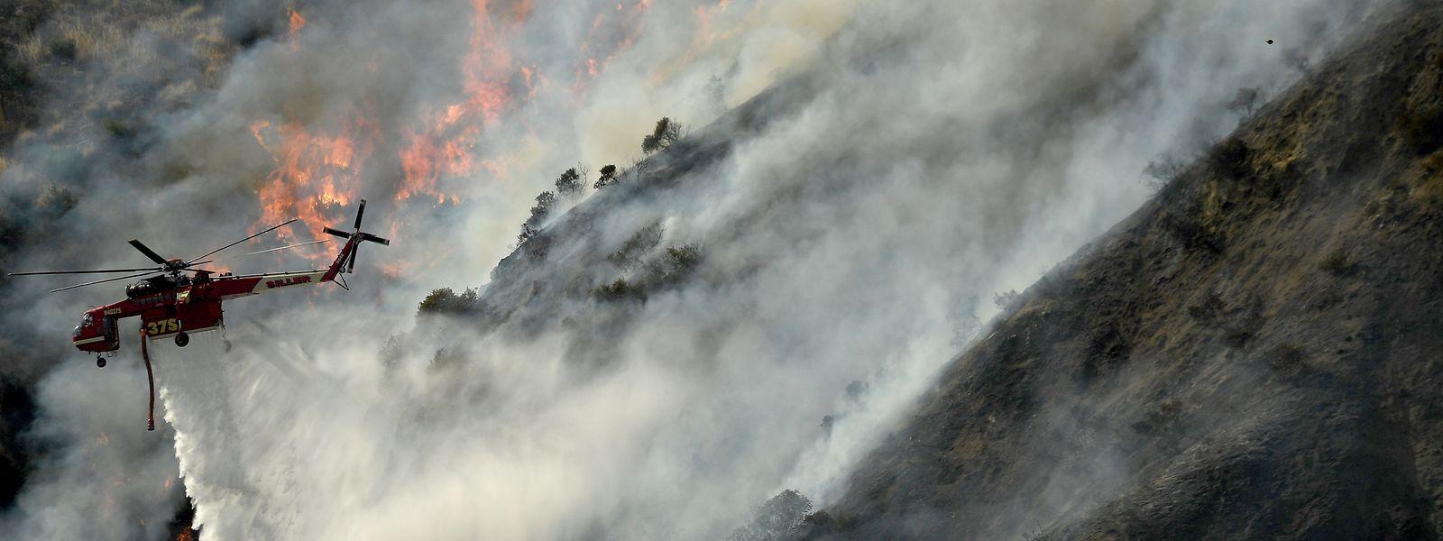 Ein Hubschrauber fliegt am Rand des Feuers entlang und wirft in der Nähe des San Gabriel Canyon Road Wasser auf die Rauchwolken ab.