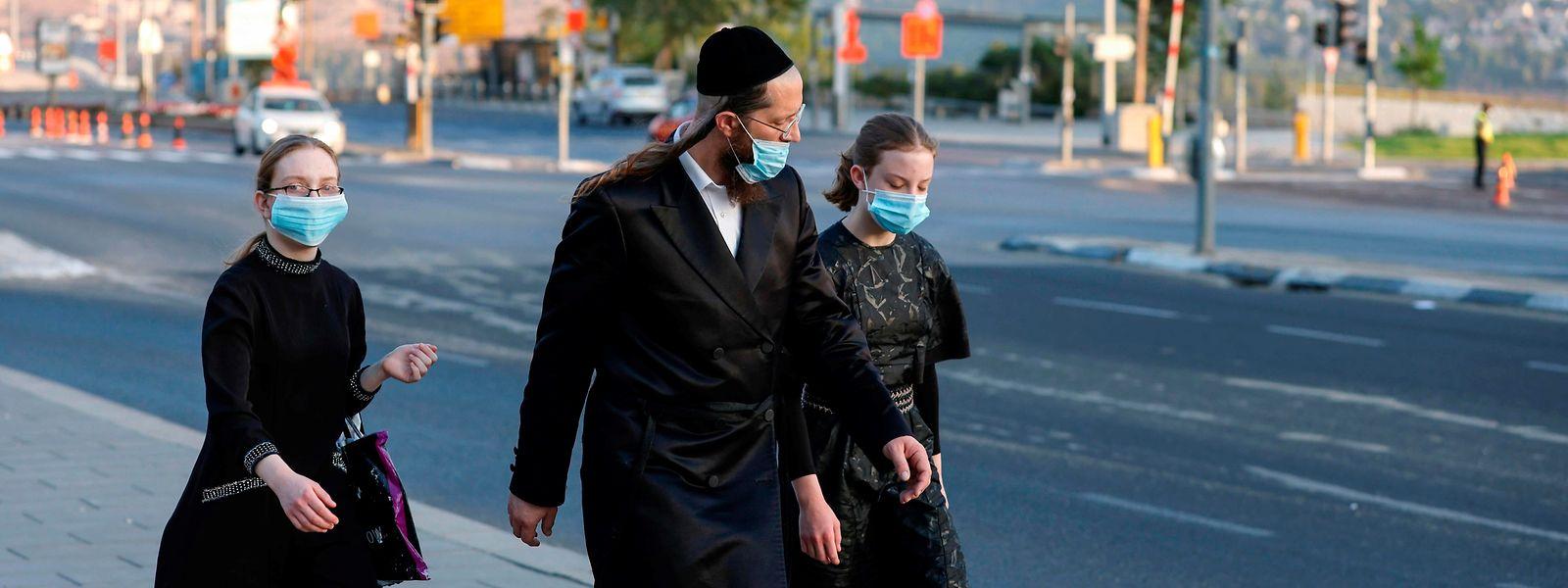 Orthodoxe Juden sind mit Schutzmaske unterwegs.
