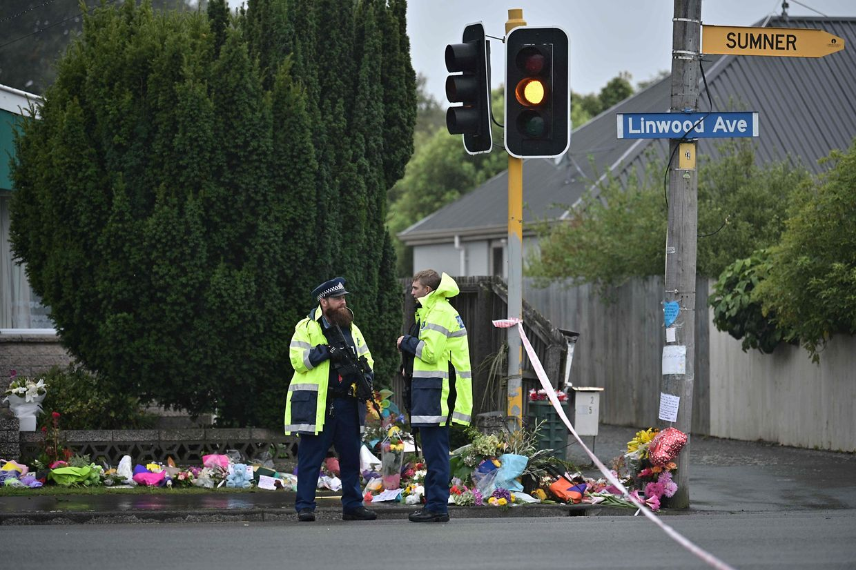 Armed police officers stand guard at a cordon blocking a road that leads to Linwood Mosque in Christchurch on March 17, 2019, two days after a shooting incident at two mosques in the city. - The death toll from horrifying shootings at two mosques in New Zealand rose to 50, police said Sunday, as Christchurch residents flocked to memorial sites and churches across the city to lay flowers and mourn the victims. (Photo by Anthony WALLACE / AFP)