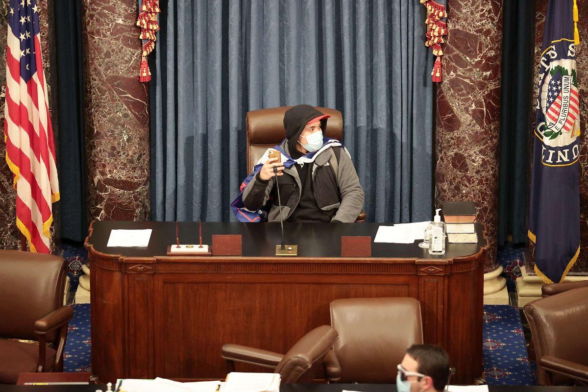 Ein Demonstrant sitzt auf dem Podest in der Senatskammer.