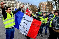 """People wearing yellow vests (gilets jaunes) chant slogans as they take part in a gathering called by the yellow vests (gilets jaunes) movement, on Place de la Republique in Lille, northern France, on January 3, 2019. - The """"Yellow Vests"""" (Gilets Jaunes) movement in France originally started as a protest about planned fuel hikes but has morphed into a mass protest against President's policies and top-down style of governing. (Photo by Philippe HUGUEN / AFP)"""