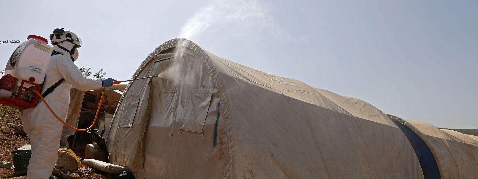 """Ein """"Weisshelm"""" beim Desinfizieren in einem syrischen Flüchtlingslager nahe der türkischen Grenze."""