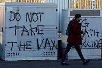 FILE PHOTO: A man walks past anti-vaccine graffiti amid the outbreak of the coronavirus disease (COVID-19) in Belfast, Northern Ireland January 1, 2021. REUTERS/Phil Noble/File Photo