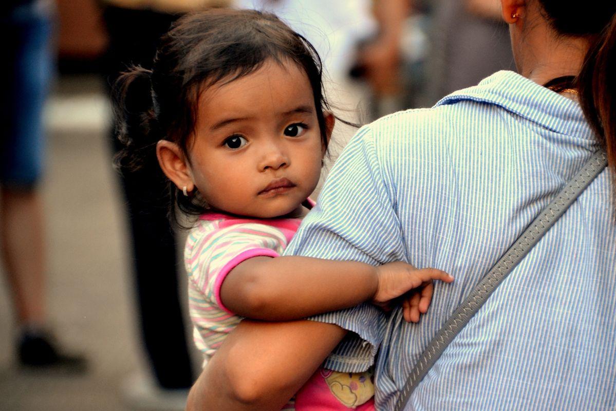 Une jeune maman et sa petite fille à un stand qui vend de l'eau de coco