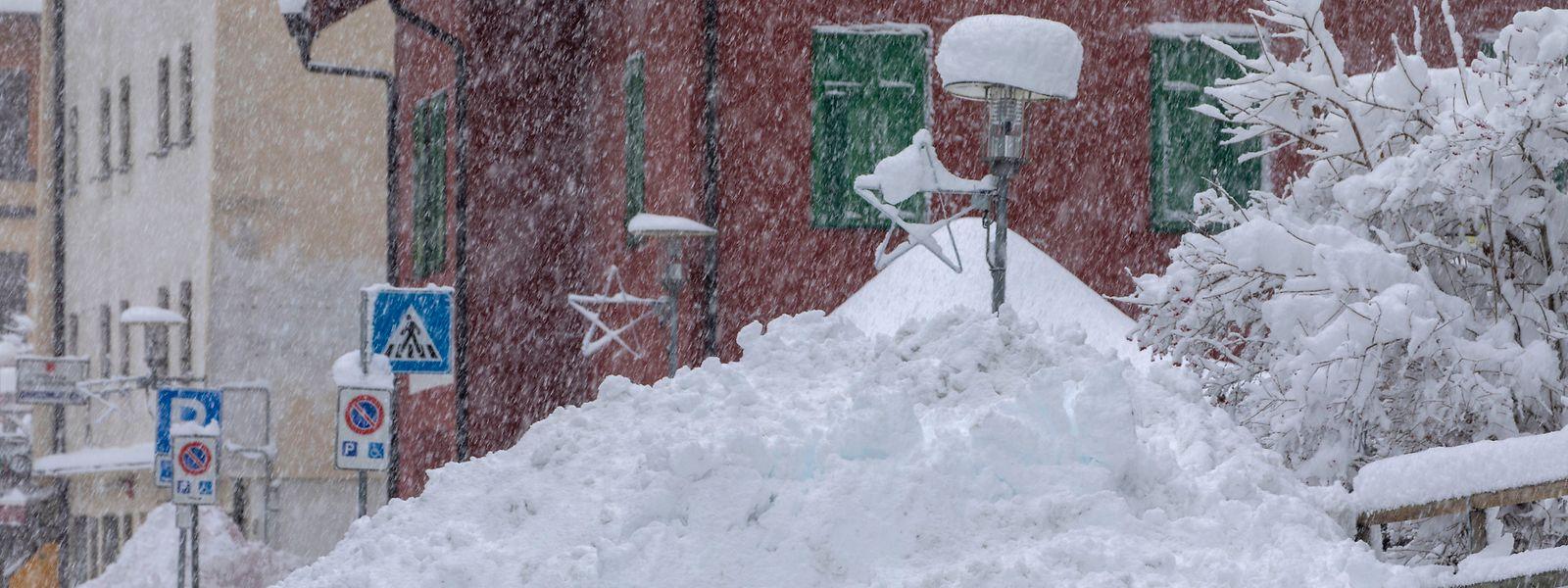 Schnee liegt hoch aufgetürmt am Straßenrand in der Gemeinde Brenner an der Grenze zwischen Italien und Österreich.
