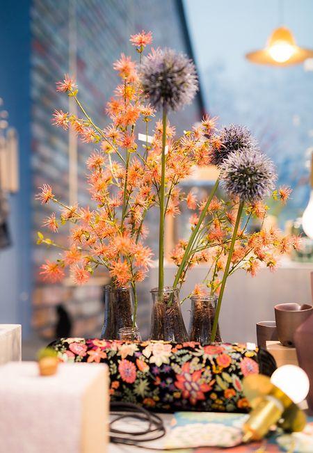 Vasen mit Blumen, florale Muster auf Kissen und warme Farben: So sieht der Trend Artisanal Gardening aus.