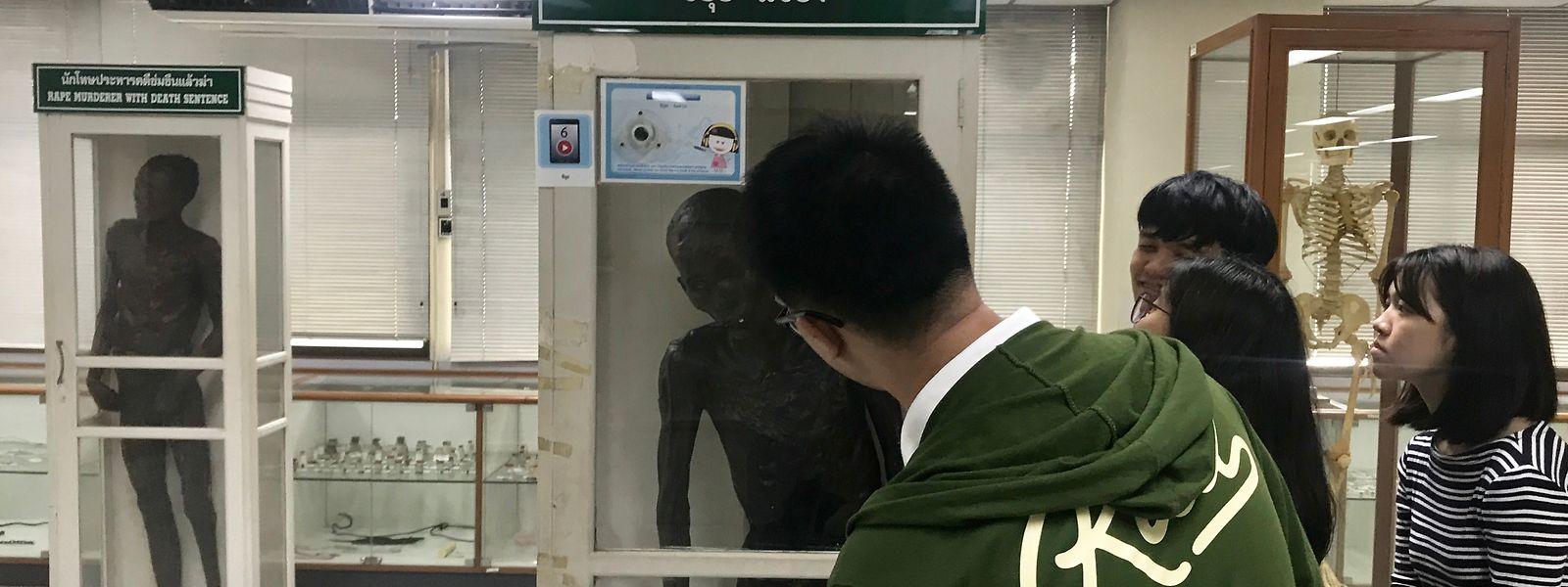 Ein Besucher betrachtet den mit Paraffin einbalsamierten Leichnam des angeblichen Mörders Si Quey.