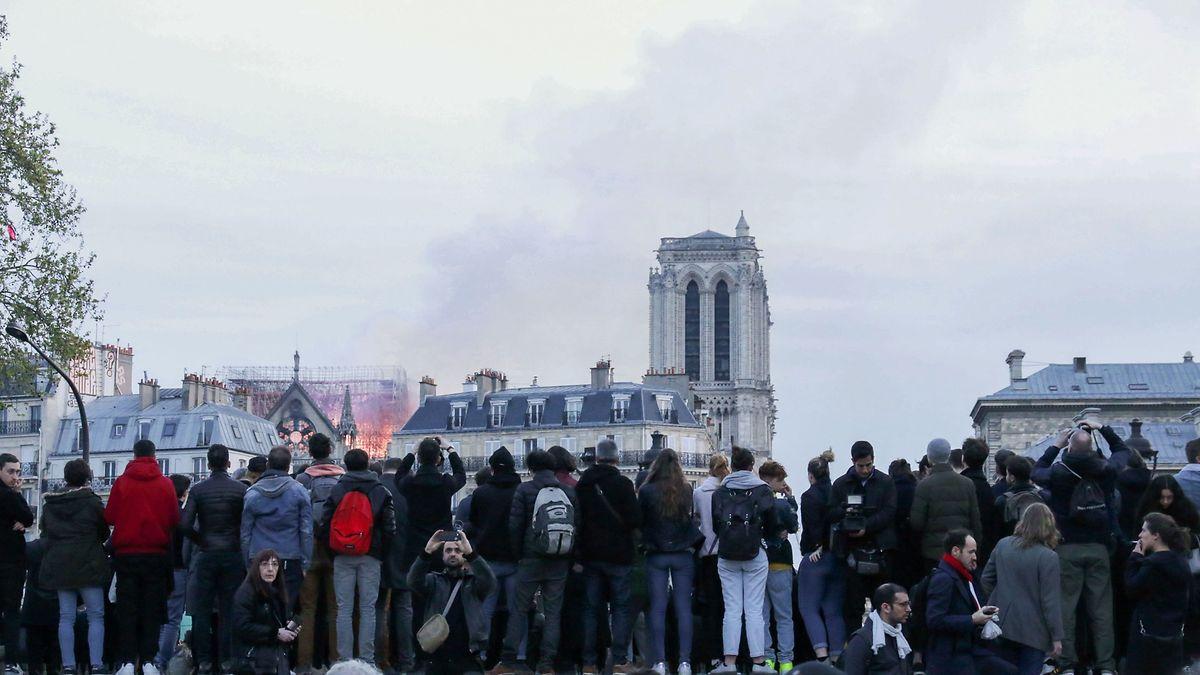 Des badauds observent les flammes sur le toit de la cathédrale depuis l'esplanade de l'Hôtel de Paris.