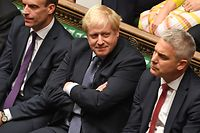 "A handout picture released by the UK Parliament shows Britain's Prime Minister Boris Johnson (C) smiling in the House of Commons in London on October 19, 2019, during a debate on the Brexit deal. - A day of high drama in parliament on Saturday saw lawmakers vote for a last-minute amendment to the deal that could force the government to seek to extend the October 31 deadline to leave. (Photo by JESSICA TAYLOR / UK PARLIAMENT / AFP) / RESTRICTED TO EDITORIAL USE - MANDATORY CREDIT "" AFP PHOTO / UK PARLIAMENT / JESSICA TAYLOR  "" - NO USE FOR ENTERTAINMENT, SATIRICAL, MARKETING OR ADVERTISING CAMPAIGNS - EDITORS NOTE THE IMAGE HAS BEEN DIGITALLY ALTERED AT SOURCE TO OBSCURE VISIBLE DOCUMENTS /"