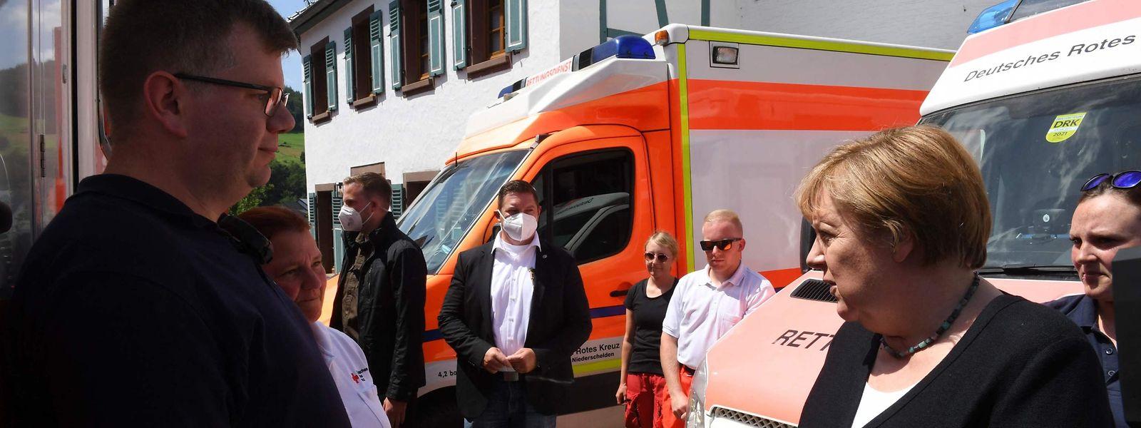 Angela Merkel im Gespräch mit Helfern des Roten Kreuzes.