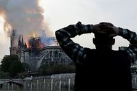 TOPSHOT - A man watches the landmark Notre-Dame Cathedral burn, engulfed in flames, in central Paris on April 15, 2019. - A huge fire swept through the roof of the famed Notre-Dame Cathedral in central Paris on April 15, 2019, sending flames and huge clouds of grey smoke billowing into the sky. The flames and smoke plumed from the spire and roof of the gothic cathedral, visited by millions of people a year. A spokesman for the cathedral told AFP that the wooden structure supporting the roof was being gutted by the blaze. (Photo by Geoffroy VAN DER HASSELT / AFP)