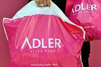 ARCHIV - 31.05.2011, Bayern, München: ILLUSTRATION - Plastiktüten der Textil-Einzelhandelskette Adler Modemärkte werden vor einer Filiale in Eching getragen. Die Adler Modemärkte AG hat einen Antrag auf Eröffnung eines Insolvenzverfahrens in Eigenverwaltung gestellt. (zu dpa «Adler Modemärkte AG stellt Insolvenzantrag») Foto: Frank Leonhardt/dpa +++ dpa-Bildfunk +++