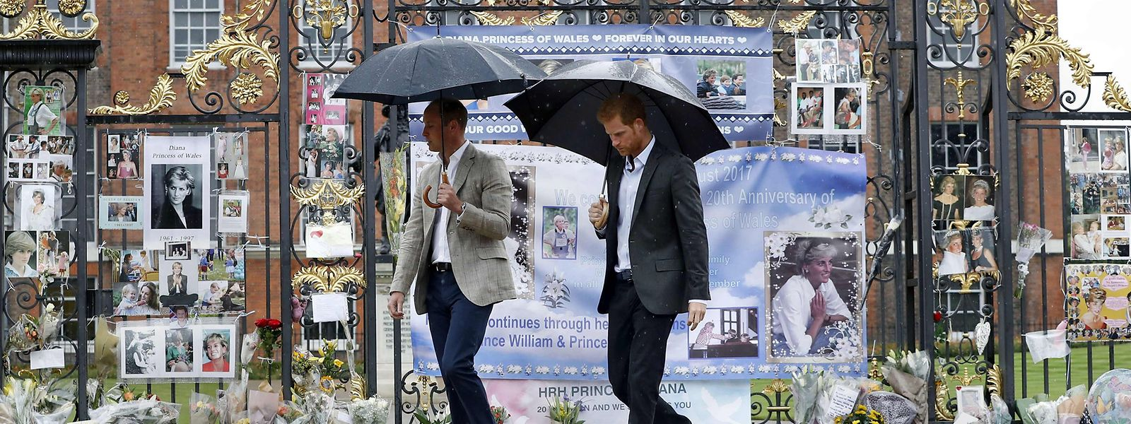 Prinz William und Prinz Harry vor den Toren des Kensington Palace, der zum 20. Todestag bereits mit Blumen und Bildern von Lady Di geschmückt ist.