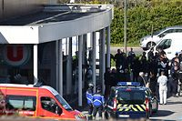 French security and police gather outside the Super U supermarket in the town of Trebes, southern France, where a man took hostages killing at least two before he was killed by security forces on March 23, 2018.   Security forces killed a gunman who first hijacked a car in nearby by Carcassonne, killing a passenger and injuring the driver, before shooting a policeman who was out jogging with his colleagues nearby. He then drove to a Super U supermarket in the town of Trebes and holed up there for more than three hours with hostages, killing at least two other people, according to sources. / AFP PHOTO / PASCAL PAVANI