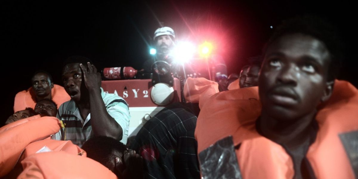 """TOPSHOT - A handout picture taken in the search and rescue zone in the Mediterranean sea on June 9, 2018 and released on June 11, 2018 by SOS Mediterranee NGO shows migrants being rescued before boarding the French NGO's ship Aquarius. The EU on June 11, 2018 called on Italy and Malta to reach a """"swift resolution"""" to allow the Aquarius, a search and rescue ship run in partnership between """"SOS Mediterranee"""" and Doctors without borders (MSF), carrying hundreds of migrants to dock, saying it was a """"humanitarian imperative"""". Some 629 people, including pregnant women and scores of children, were saved by SOS Mediterranean on JUne 9 and are stuck aboard the French NGO's ship Aquarius, which is currently between Malta and Sicily waiting for a secure port. / AFP PHOTO / SOS MEDITERRANEE / Karpov / RESTRICTED TO EDITORIAL USE - MANDATORY CREDIT """"AFP PHOTO / KARPOV / SOS MEDITERRANEE"""" - NO MARKETING NO ADVERTISING CAMPAIGNS - DISTRIBUTED AS A SERVICE TO CLIENTS"""