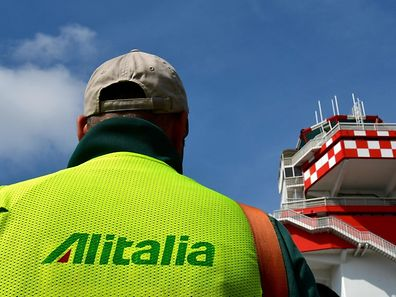 (FILES) This file photo taken on March 20, 2017 shows an Alitalia air transport employee taking part in a protest at Rome's Fiumicino airport.  Alitalia workers have rejected a restructuring deal from the company's management and unions to save the ailing carrier, Italian media reported on April 24, 2017. Almost 90 percent of its 12,500 employees had participated in a vote and more than half those taking part opposed the deal, with more than a third of ballots still to be counted. / AFP PHOTO / Alberto PIZZOLI