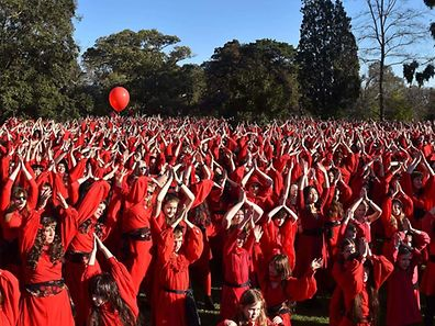Kate Bush fans perform a dance during a celebration to mark 'The Most Wuthering Heights Day Ever' in Melbourne on July 16, 2016. Thousands of Kate Bush fans put on their best billowy red dresses and danced en masse in Melbourne on July 14 to one of the singer's most iconic songs Wuthering Heights. / AFP PHOTO / Paul Crock