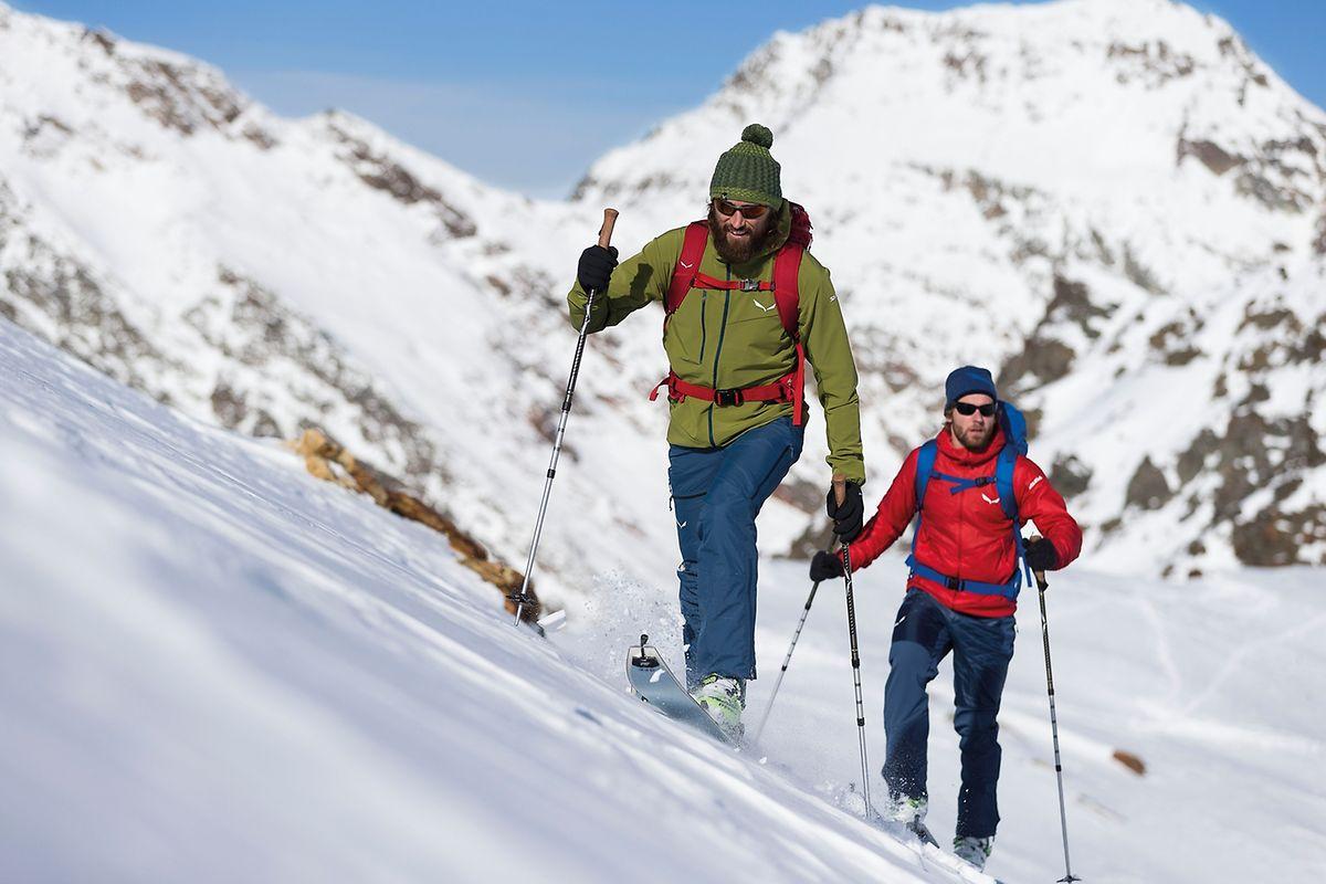 Bergauf schwitzen, bergab kalter Wind: Das Skitourengehen beeinflusst die Wintersportmode, die sich immer mehr am funktionalen Zwiebel-System orientiert. (Vorne: Jacke 170 Euro, Hose 280 Euro, Beanie 30 Euro, Hinten: Jacke 200 Euro, Hose 200 Euro, Beanie 35 Euro).
