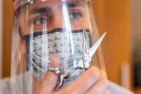ARCHIV - 04.05.2020, Sachsen, Dresden: Ein Friseur hält in einem Friseurstudio eine Haarschneideschere in der Hand und trägt dabei einen Mundschutz und ein Gesichtsschutzschild. (zu dpa «Waschen, Schneiden, Föhnen, Sparen - Wie Friseure unter Corona leiden» vom 02.07.2020) Foto: Robert Michael/dpa-Zentralbild/dpa +++ dpa-Bildfunk +++