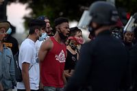 TOPSHOT - Protesters react in front of police as they gather in downtown Los Angeles on May 27, 2020 to demonstrate after George Floyd, an unarmed black man, died while being arrested by a police officer in Minneapolis who pinned him to the ground with his knee. - Outrage has grown across the country at Floyd's death on May 25, fuelled in part by bystander cellphone video which shows him, handcuffed and in the custody of four white police officers, on the ground while one presses his knee into the victim's neck. (Photo by Agustin PAULLIER / AFP)